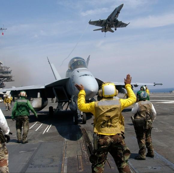Hornet sobrevoa CVN 63 enquanto Super Hornet é preparado para lançamento - foto Marinha dos EUA
