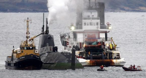 Rebocadores se mover para ajudar a Royal Navy submarino nuclear HMS Astute, depois que encalhou em águas rasas ao largo da ilha de Skye, na Escócia, Sexta-feira 22 de outubro de 2010. O Ministério da Defesa insistiu que o acidente não foi um incidente nuclear, que o submarino permaneceu estanque, e que não há nenhuma indicação de todos os problemas ambientais, como resultado do acidente. O Astute é o maior e mais poderoso submarino de ataque já construído para a Royal Navy, e mede cerca de cem metros da proa à popa, e é mais do que dez ônibus de Londres