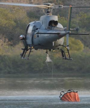 Helicóptero da Marinha pegando água para jogar sobre o incêndio