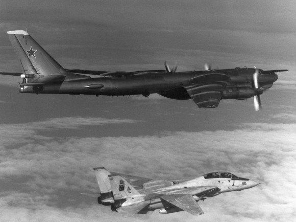 Air-to-air right side view of a Soviet TU-95 Bear-D aircraft with F-14A Tomcat aircraft from the fighter squadron (VA-11) below.
