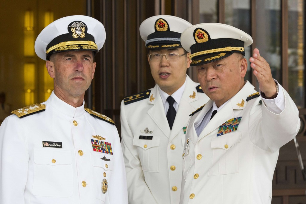 U.S. Chief of Naval Operations Adm. John Richardson, left, listens to Commander of the Chinese Navy Adm. Wu Shengli, right, at Chinese Navy Headquarters in Beijing. The top U.S. admiral said friendly exchanges with China's navy are conditional on safe and professional interactions at sea. Richardson's comments Wednesday, July 20, 2016, follow several fractious encounters between the two sides' ships and planes in and over the disputed South China Sea. (AP Photo/Ng Han Guan, Pool, File)