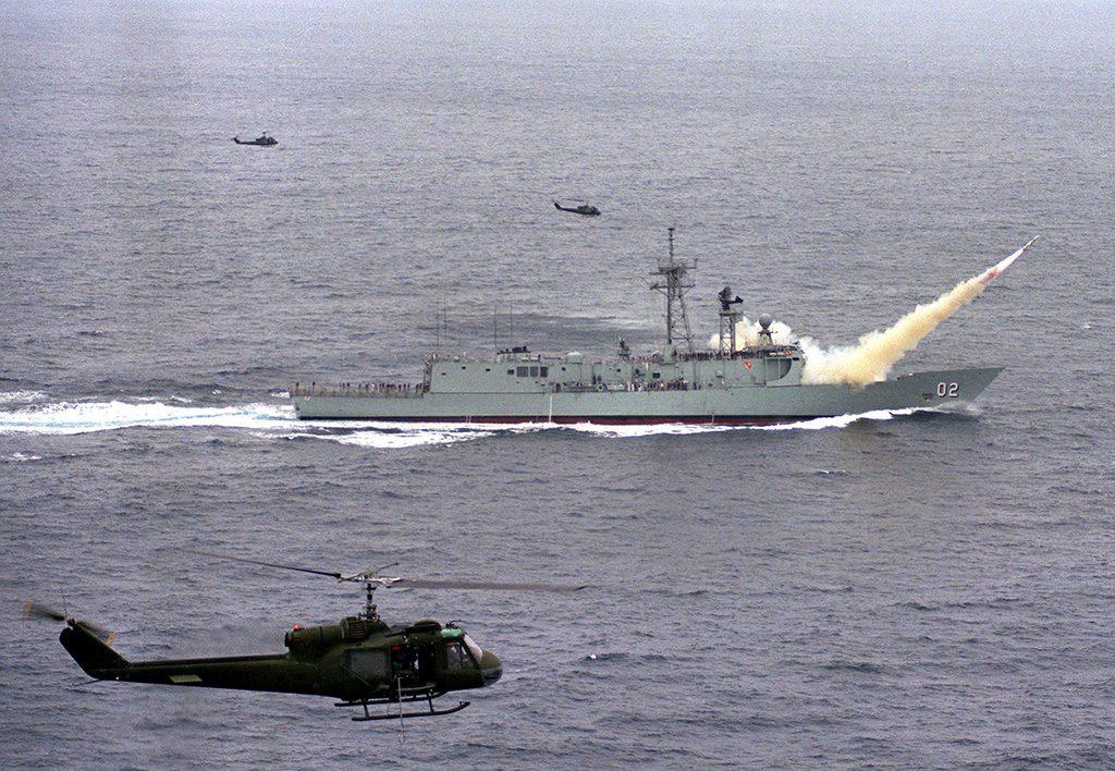 HMAS Canberra (F-02) lançando míssil Harpoon, enquanto helicópteros UH-1 Iroquois fazem a cobertura aérea do lançamento