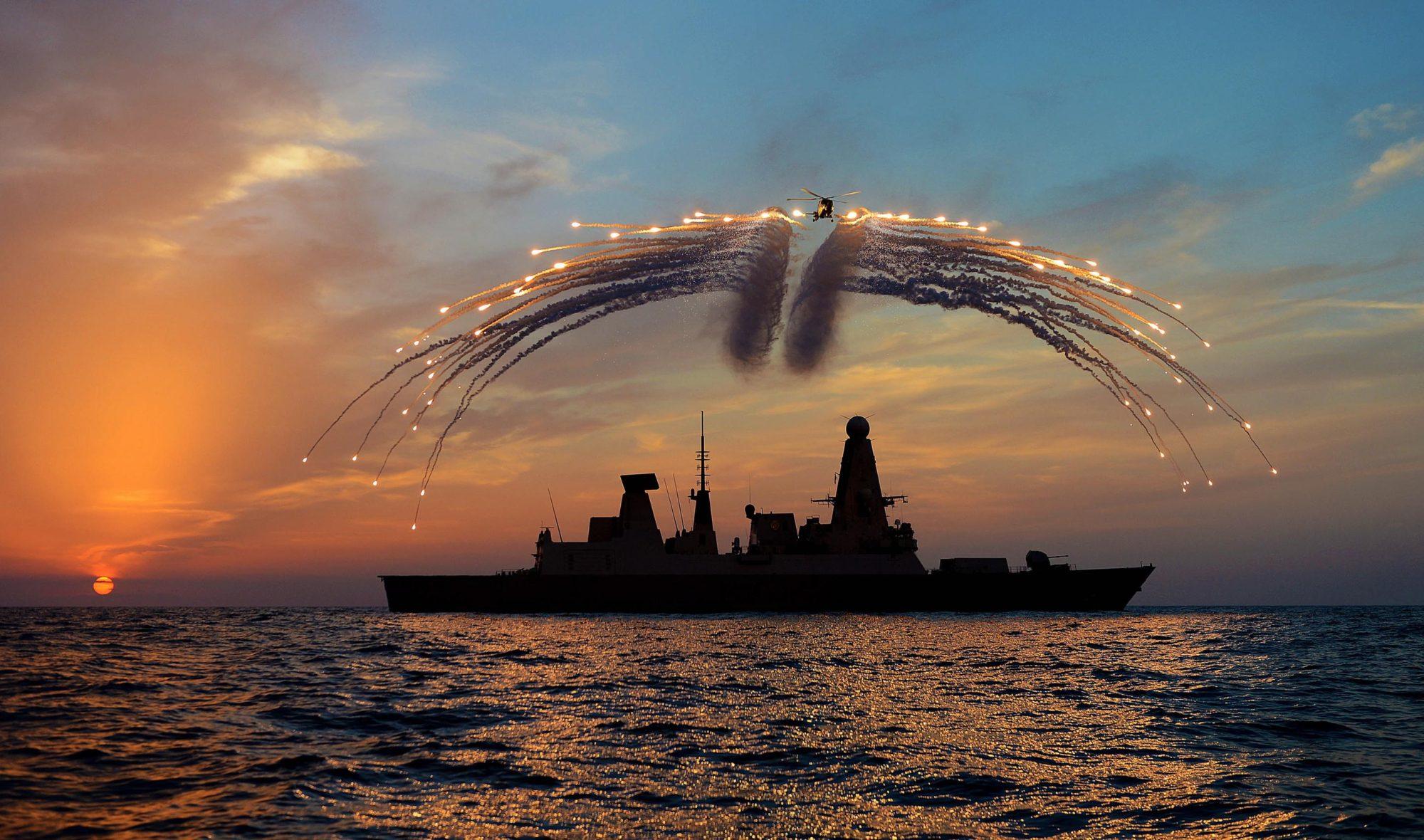Helicóptero Lynx lançando flares sobre um destróier Type 45 da Royal Navy
