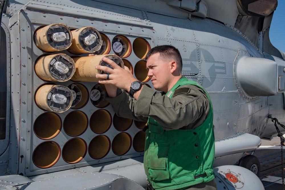 Militar carregando sonoboias em um helicóptero MH-60R