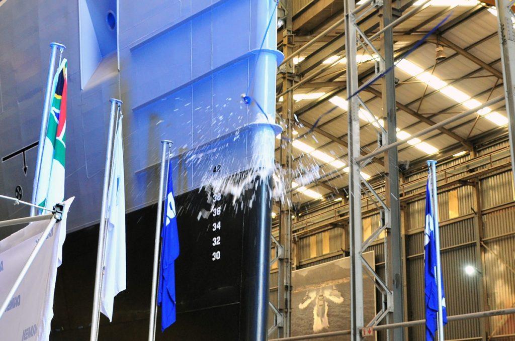 Cerimônia de Bênção da Marinha da África do Sul: Durante o evento, o navio foi abençoado e uma garrafa de champanhe foi quebrada na proa como é o costume